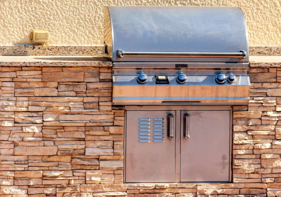 An outdoor kitchen with a grill mounted in a stone counter.