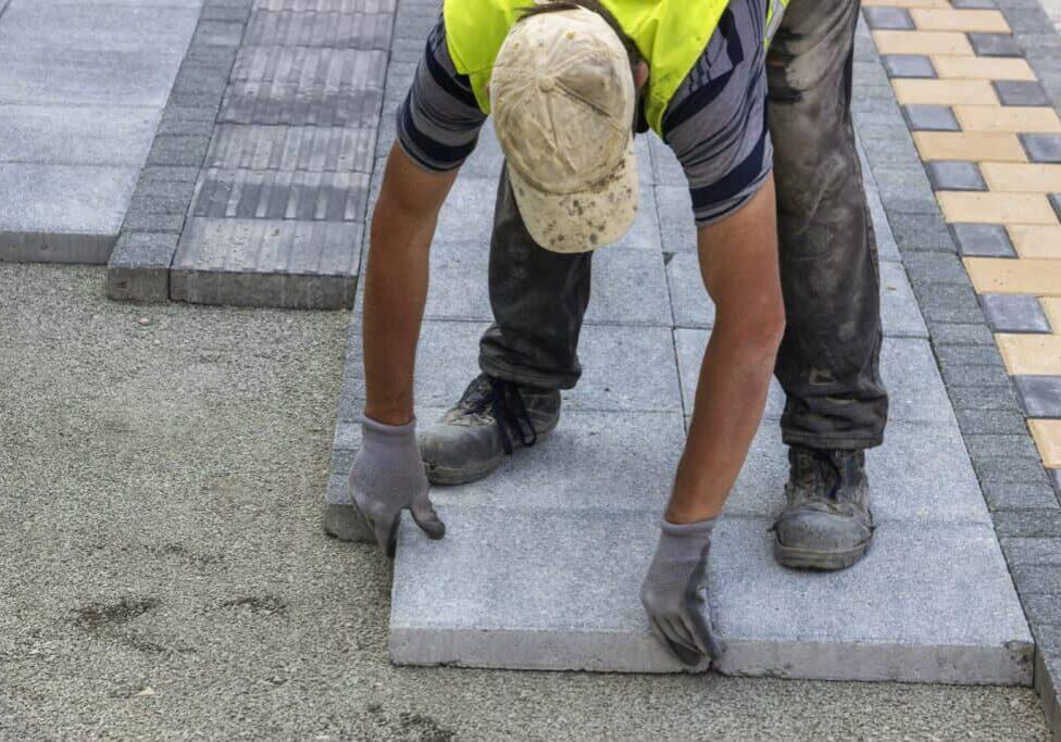 Sidewalk paver installation in progress. Sidewalk revitalization. Focus on worker.