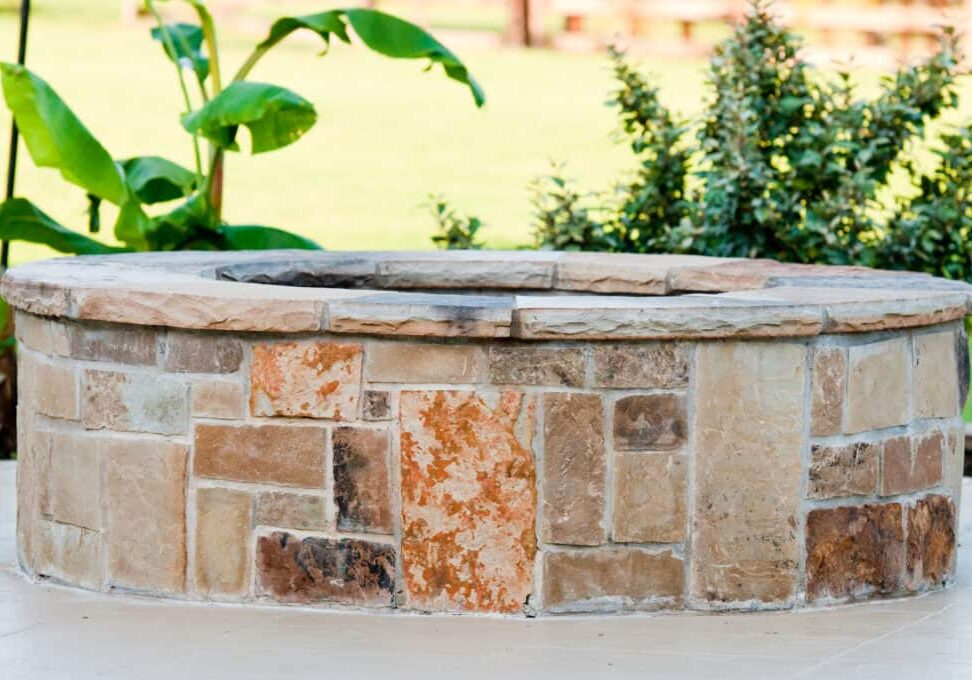 Residential outdoor stone firepit on concrete patio with landscaping and plants in background.